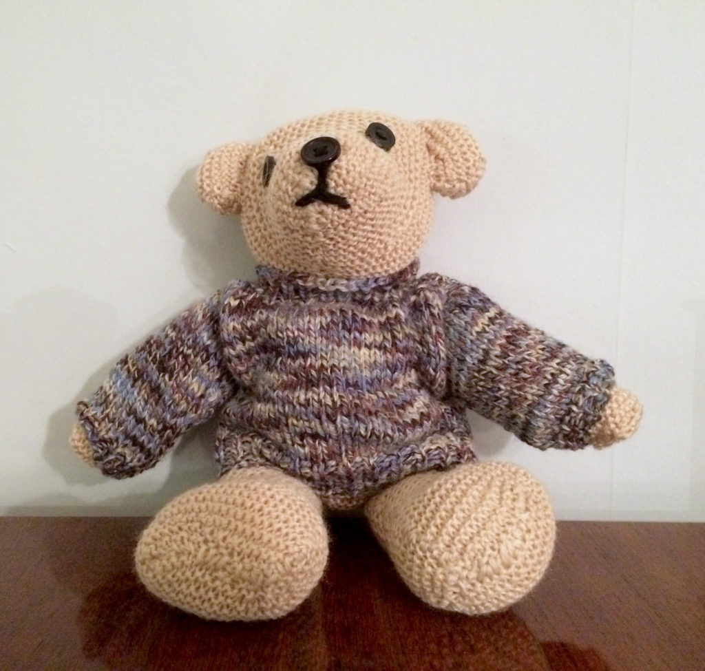 Knitted teddybear with a slightly wonky face wearing a multicoloured knitted jumper