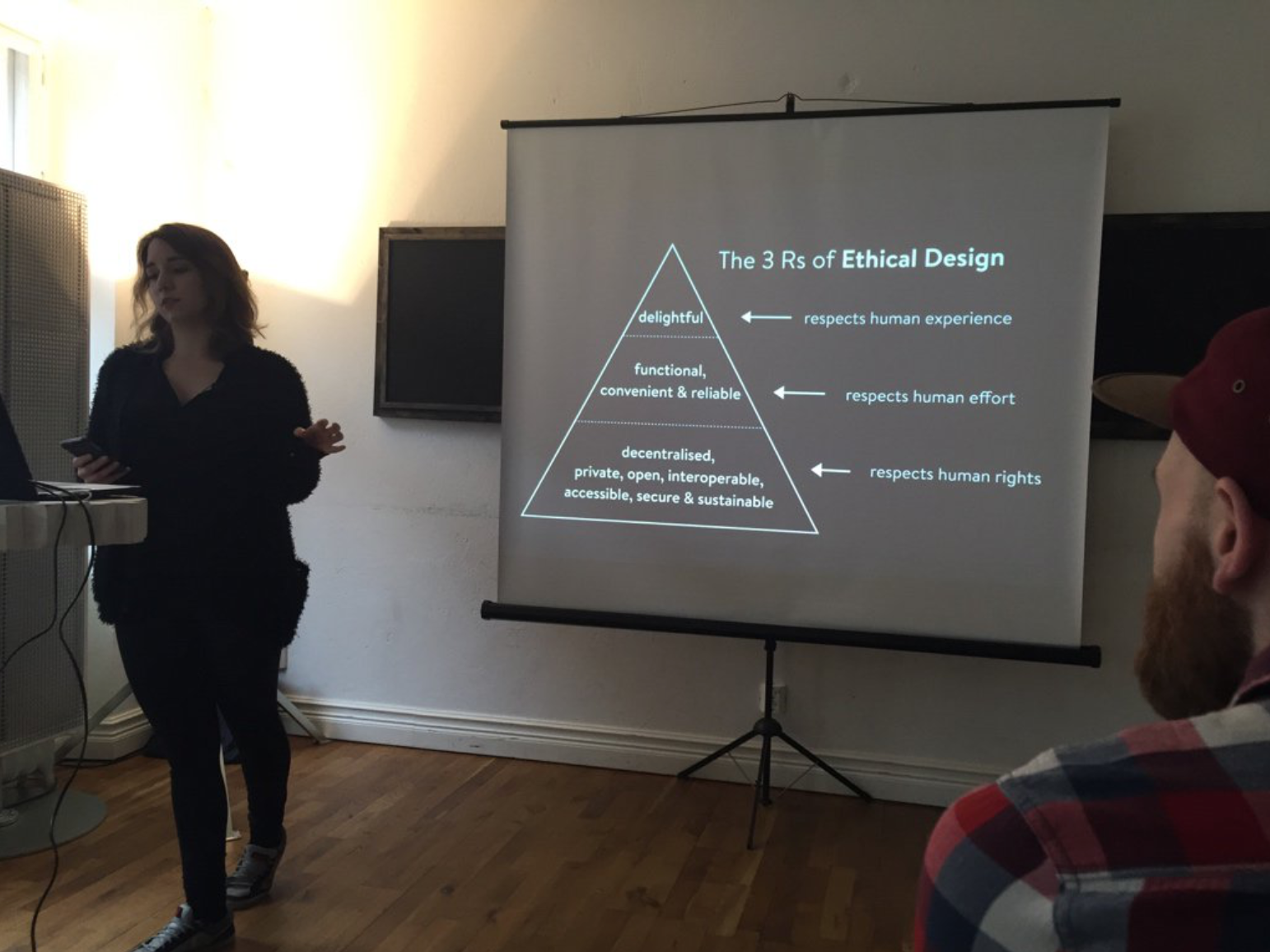 Me talking with a slide of the Ethical Design Manifesto (The 3 Rs of Ethical Design) in a fluffy black cardigan