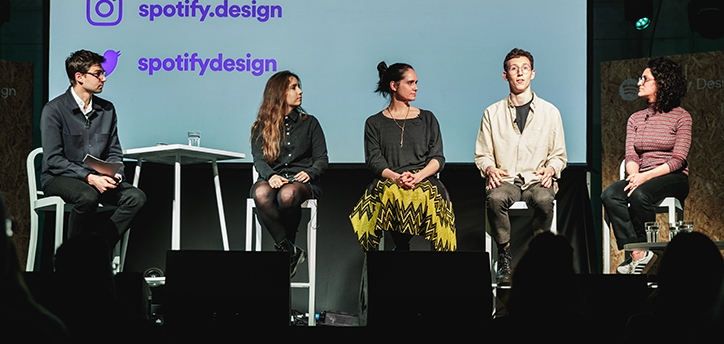 Photo of me on a panel where I am wearing a long button-up dress with a lapel microphone.