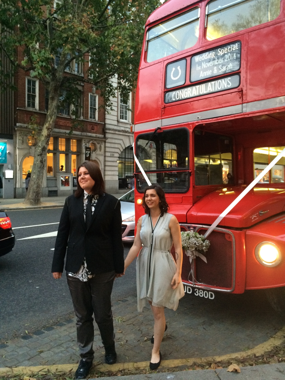 Sarah and Annie standing in front of their wedding bus