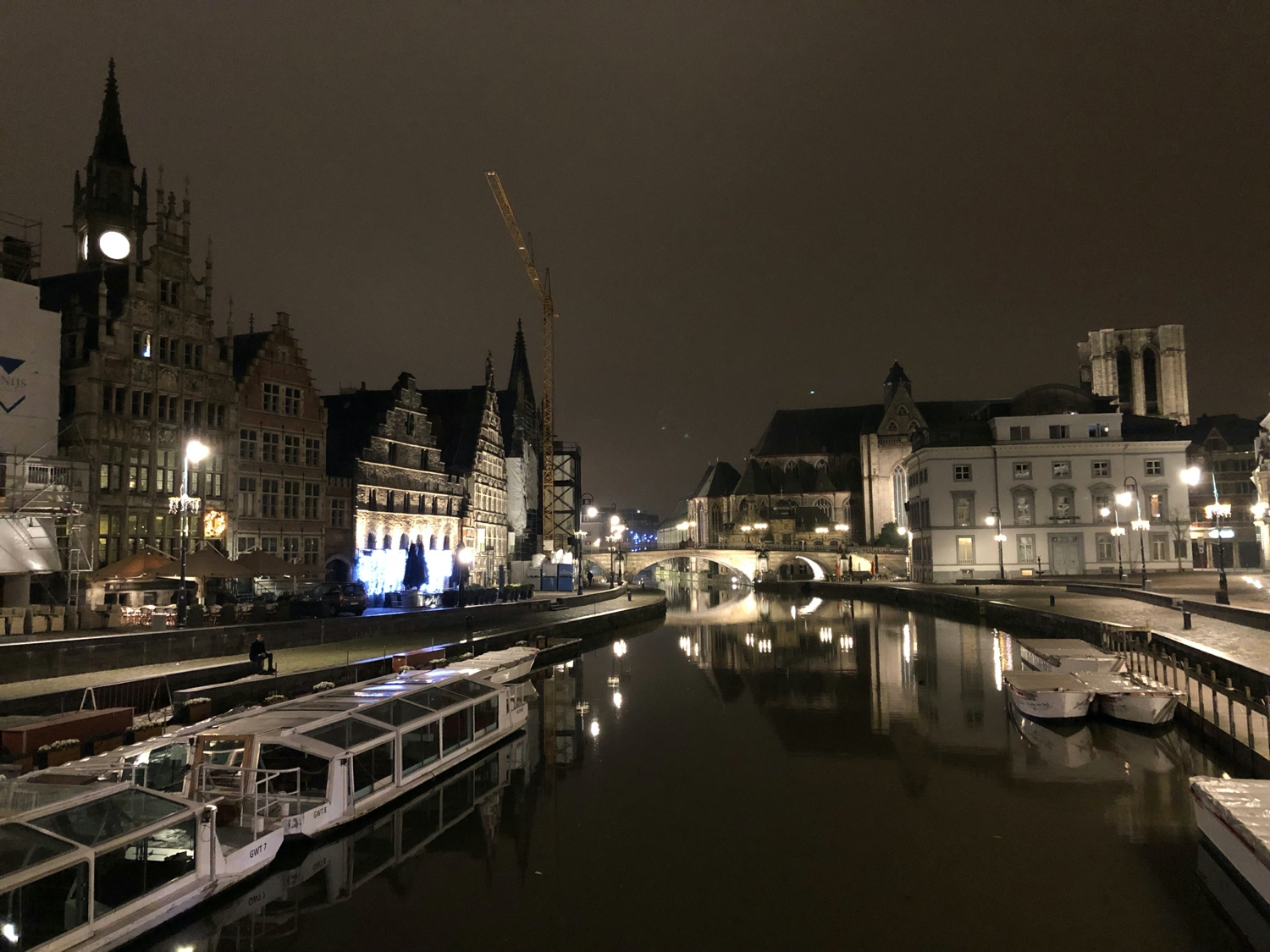 View of old buildings in Ghent over a canal at night.
