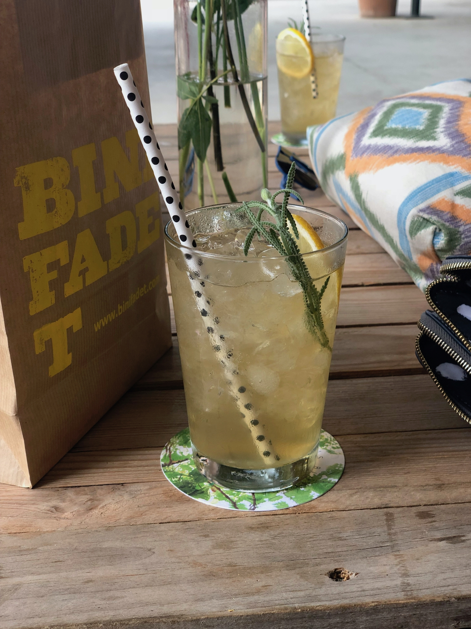 A paper bag with 'Binifadet' printed on the side, accompanied by fancy yellow Lavendar Lemonade drink.