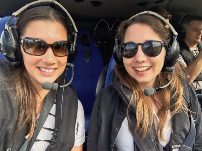 Me and my sister Emily sitting smiling in a helicopter.