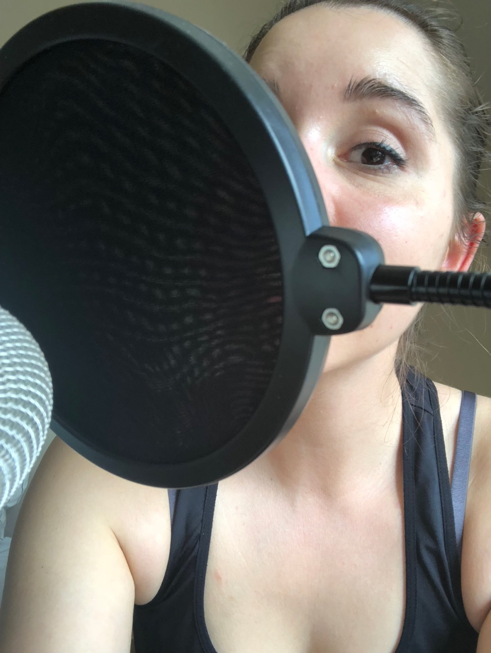 Selfie of me speaking into a pop shield in front of a microphone.