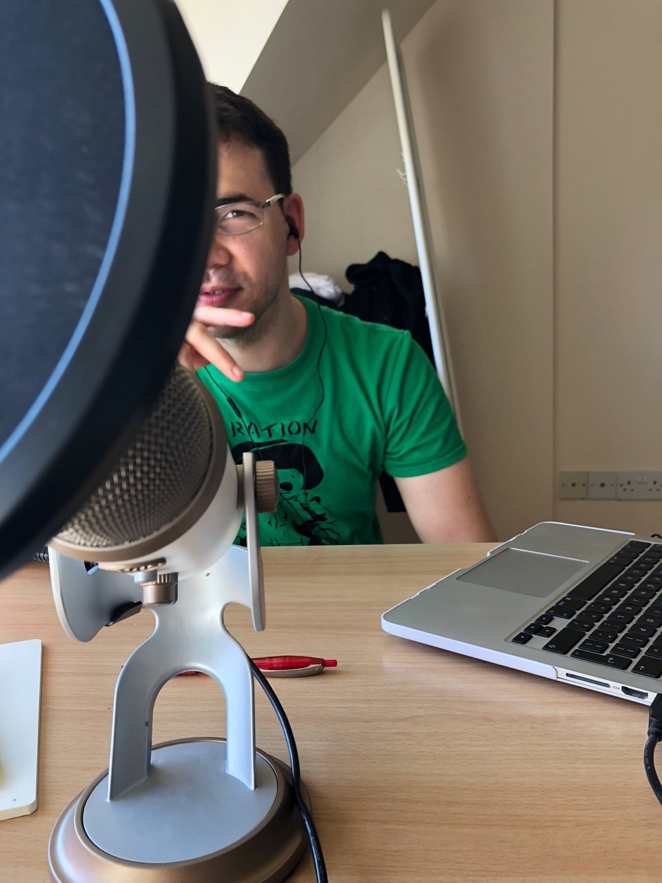 Half of Sam's head and body, partly obscured by the microphone. It's my view of him and the desk while we're recording.