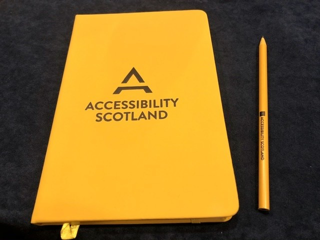 Accessibility Scotland branded notebook and pencil.