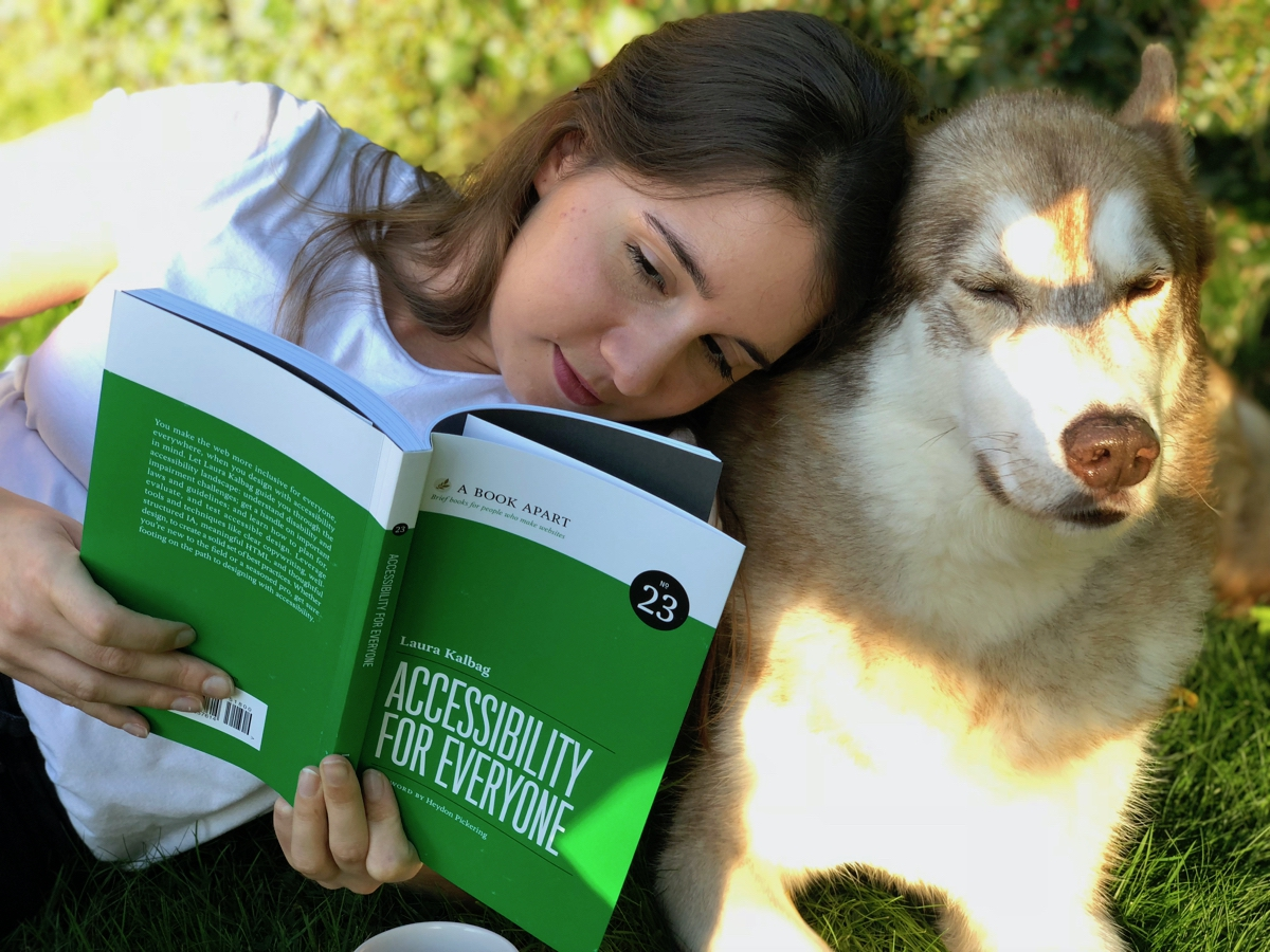 me reading Accessibility For Everyone in the garden next to Oskar the huskamute who couldn't care less.