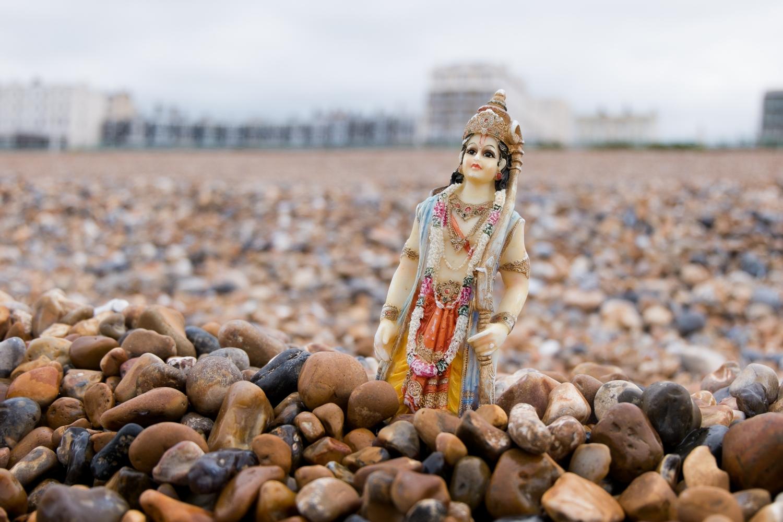 A Rama figurine, standing in pebbles on Brighton beach