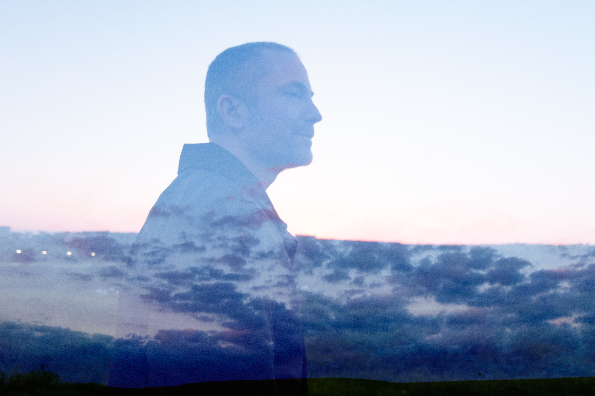 Profile of Aral, overlaid on purple and blue clouds in the sky