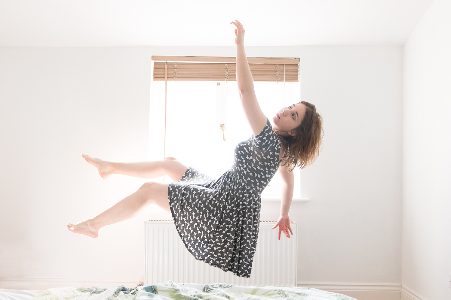 A photo of me levitating in front of a window, with my arms and legs floating around.